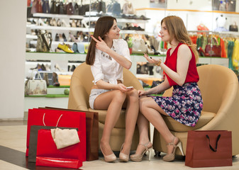 Two young girlfriends sitting in the shop and relax after shoppi