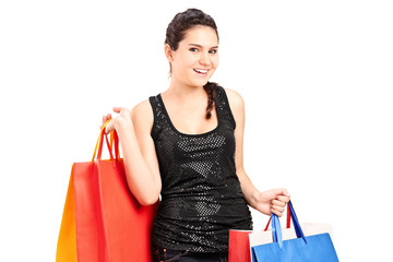 Fashionable female holding bunch of shopping bags