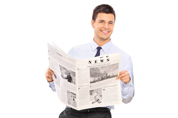 Handsome man holding a newspaper and leaning against a wall