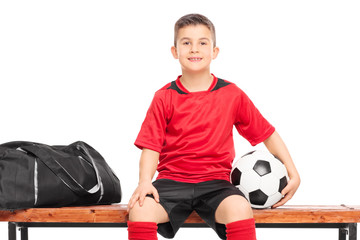 Junior soccer player sitting on a bench and holding a football