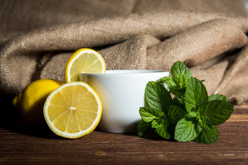 Tea with lemon and mint on wooden table