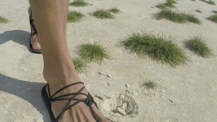 Slow motion man's feet walking on grassy beach