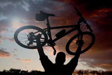 Silhouette of bicycle rider on a rock at sunset