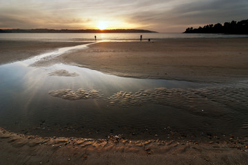 fishermen with blue sky and red on the beach at dusk