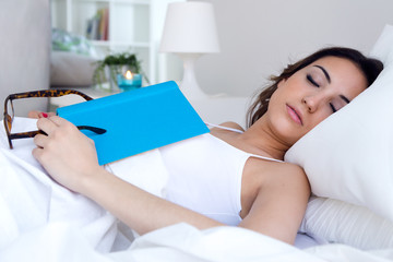 Beautiful young woman sleeping after read a book.