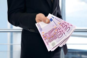A businessman holding money - Euro (EUR)
