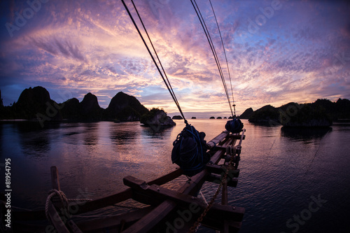 Foto op Plexiglas Indonesië Sunset Over Islands and Schooner