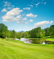 Golf field. Landscape with green grass and beautiful blue sky