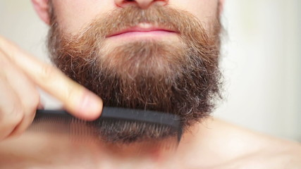 Сare beard - man combing his mustache and beard