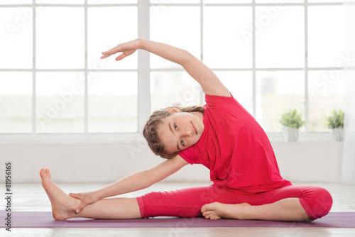 Tuinposter Gymnastiek Little girl making gymnastics and stretching