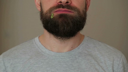 Beared man eats a hamburger
