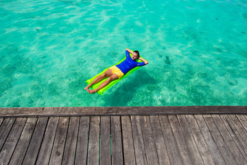 Young man relaxing on inflatable mattress in the sea