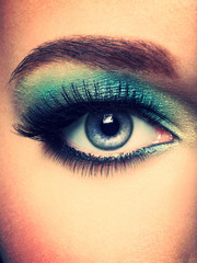 Woman's eye with green eye make-up. Long eyelashes