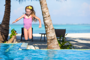 Smiling adorable girl having fun in outdoor swimming pool