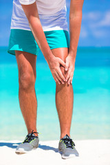 Male athlete suffering from pain in leg while exercising on