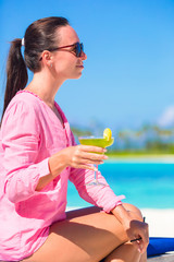 Young woman with tasty cocktail on white tropical beach