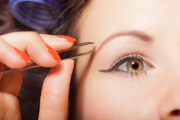 Girl tweezing eyebrows closeup