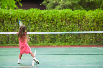Little girl playing tennis on the court