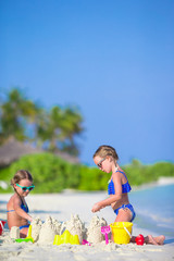 Happy little girls playing with beach toys during tropical