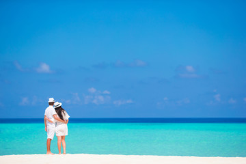 Back view of young couple on white beach at summer vacation