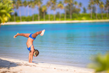 Adorable little girl having fun making cartwheel on tropical
