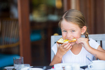 Little adorable girl eating bread with butter and honey on