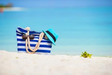 Blue bag, straw hat, sunglasses on white beach