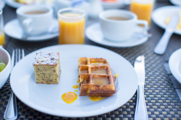 Delicious waffles, cake, coffee and juice served for breakfast