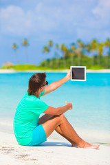 Young man with laptop at tropical beach