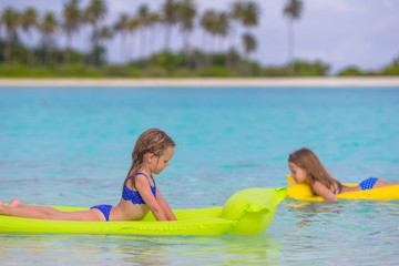Adorable little girls on air inflatable mattress in the sea