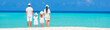canvas print picture - Rear view of young beautiful family on white tropical beach