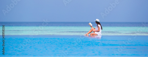 Young girl reading book near swimming pool - 81958336
