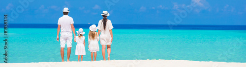 Leinwandbild Motiv Rear view of young beautiful family on white tropical beach