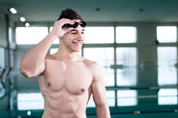 Young muscular swimmer with protective glasses