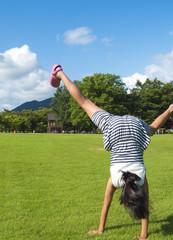芝生広場で側転の練習をする女の子