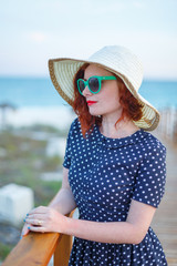 Red-haired girl in a hat and sunglasses