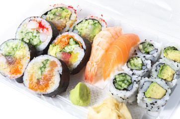 Assorted sushi rolls and nigiri in a transparent plastic tray ag