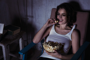 woman with popcorn watching movie and laughing