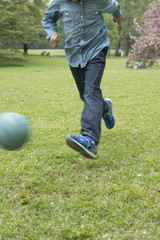 Boy playing with ball in grassland
