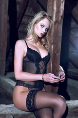 Sexy woman in underwear cuffed to timber