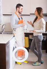 Workman and client near washing machine