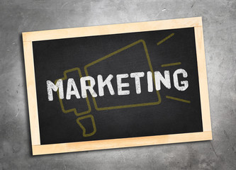 marketing word and yellow megaphone icon on blackboard lay on gr