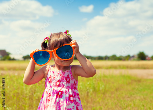 Happy little girl with big sunglasses walking on the field - 81968183