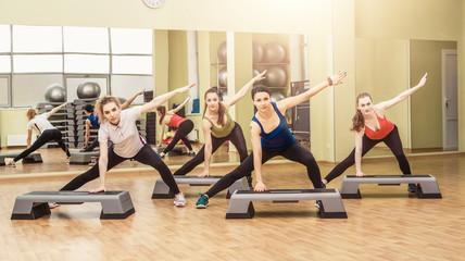 Group of women making step aerobics