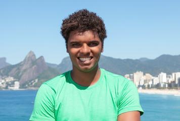 Fröhlicher Latino im grünen Shirt am Strand von Ipanema