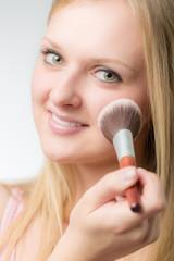 Junge Frau pudert sich das Gesicht