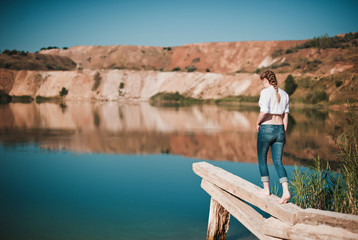 Beautiful young  woman going on the pier on a blue lake,