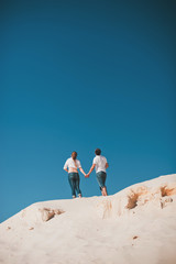 couple sit back and hold hands against the blue sky
