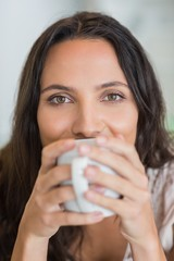 Pretty brunette drinking a mug