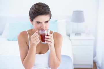 Thoughtful  woman drinking cup of tea